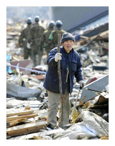 An elderly man looks for his house through the rubble in Rikuzentakata, Iwate Prefecture, northern Japan.