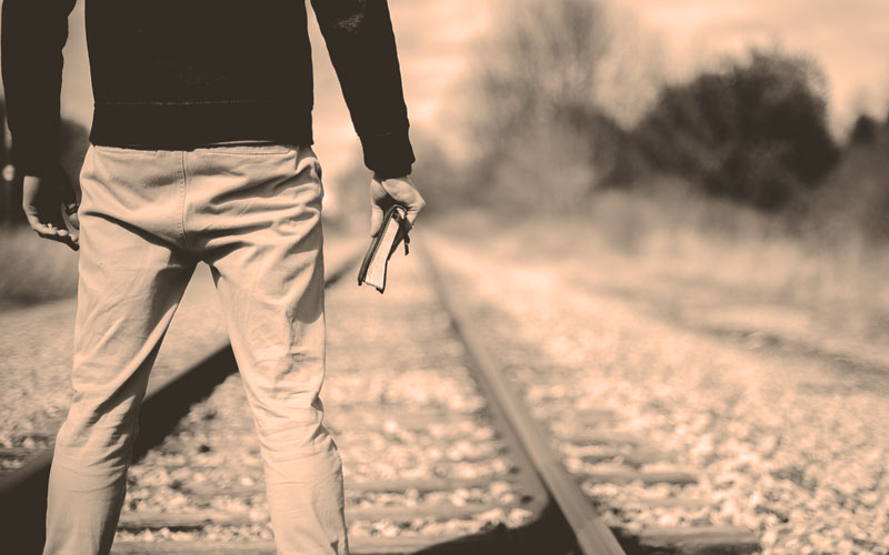 Man with Bible Standing on the Train Tracks